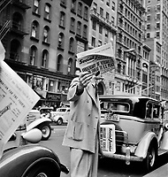 Street Corner Saint: Social Justice newspaper, founded by Father Coughlin, sold on important street corners and intersections in New York City. 1939.<br /> <br /> Photo by Dorothea Lange
