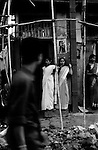 A local man inspects the goods of two young prostitutes in the market place of the red light district. 50% of prostitutes in India enter the trade as minors.<br />