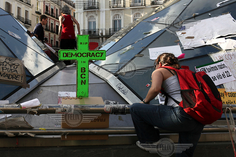Demonstrators climb onto the roof of a building, past a green sign in the shape of a crucifix which says, 'RIP Democracy in BCN'. In May 2012, following a worsening financial crisis and a deepening recession in Spain, thousands of people started to gather in Spanish cities to protest against austerity, the global financial system, high unemplyment rate (Spain's is the highest rate in Europe) and the lack of opportunities. The protest movement has become known as 'los indignados' (the indignant ones).