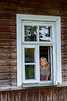Estonia, Muhu Island. Muhu Jaanalind, guest house and farm. Ingrem Raidjoe (Daughter & owner), Helena Erik (mother & owner). Little girl in the window.