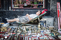 "A Chinese street vendor takes a rest on a chair in the streets of PingYao, China, July 30, 2014. <br /> <br /> This image is part of the series ""24/7"", an ironic view on restless and fast-growing Chinese economy described through street vendors and workers sleeping during their commercial daily activity. <br /> <br /> © Giorgio Perottino"