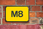Letter M number 8 yellow sign on brick wall, used to spell Mate in text messages