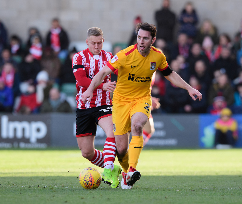 Northampton Town's John-Joe O'Toole under pressure from Lincoln City's Danny Rowe<br /> <br /> Photographer Chris Vaughan/CameraSport<br /> <br /> The EFL Sky Bet League Two - Lincoln City v Northampton Town - Saturday 9th February 2019 - Sincil Bank - Lincoln<br /> <br /> World Copyright © 2019 CameraSport. All rights reserved. 43 Linden Ave. Countesthorpe. Leicester. England. LE8 5PG - Tel: +44 (0) 116 277 4147 - admin@camerasport.com - www.camerasport.com