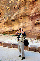 """Jordan. Petra.The archeological site is part of the UNESCO world heritage project.  The Nabataeans were an arabian industrious tribe which settled down in southern Jordan 2000 years ago. Petra is located at the bottom of a spectacular deep gorge surrounded by mountains. German tourist takes pictures while walking down the """"Siq"""", a narrow and long path through a fault due to a prehistoric earthquake.  © 2002 Didier Ruef"""