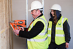 © Joel Goodman - 07973 332324 .  04/02/2014 . Manchester , UK . Mike Kane tries the nail gun , watched over by an apprentice joiner . Ed Balls , MP for Morley and Outwood and Shadow Chancellor of the Exchequer the Labour Party , joins Labour candidate Mike Kane on the campaign trail ahead of the Wythenshawe and Sale East by-election , following the death of MP Paul Goggins . They visit apprentices at the Leybrook Road building site in Wythenshawe where apprentice builders work on bungalows built for affordable rent . Photo credit : Joel Goodman