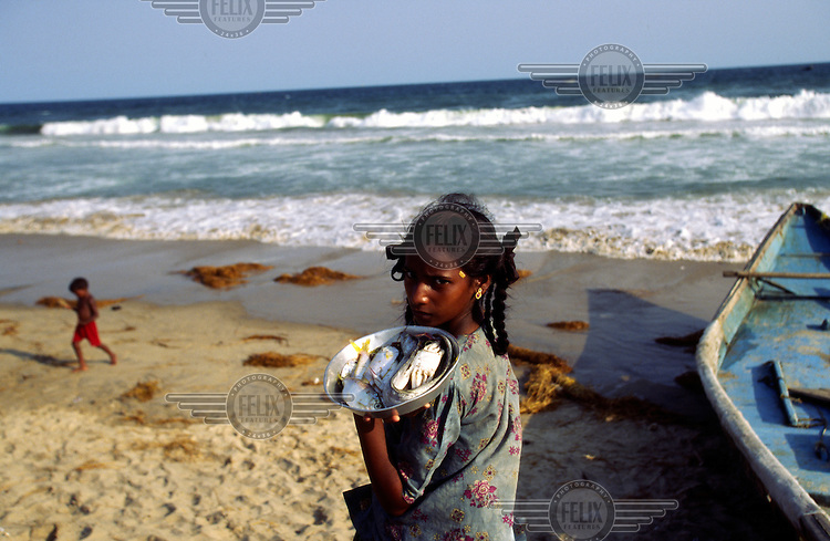A girl sells fish on the beach.