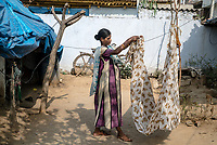 8 months pregnant, 21 year old Jhansi Aitharam carries on with household chores in the courtyard of her house in Ambedkar Nagar, Medak, Telangana, India.