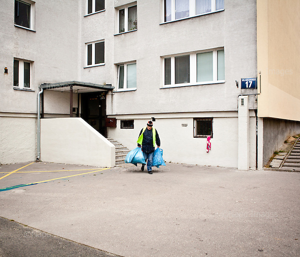 Warsaw, Poland, November 2011:.Tomasz, employee of Ekon Association, collecting recyclable materials at the Ursynow housing estate. .Ekon Association in Warsaw is a recycling plant that provides jobs for people with learning difficulties or mental health issues; who would otherwise find it difficult to get work. .(Photo by Piotr Malecki / Napo Images)..Warszawa, Listopad 2011:.Maciek, pracownik stowarzyszenia Ekon, zbiera surowce wtorne od mieszkancwo osiedla Ursynow. Ekon zajmuje sie recyklingiem odpadow i zatrudnia ludzi uposledzonych, lub chorych psychicznie, ktorzy inaczej mieliby trudnosci ze znalezieniem pracy..Fot: Piotr Malecki / Napo Images.