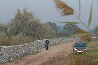 Police officer looking for illegal migrants patrols next to the razor wire fence on the border between Hungary and Serbia near Roszke (about 174 km South of capital city Budapest), Hungary on August 30, 2015. ATTILA VOLGYI
