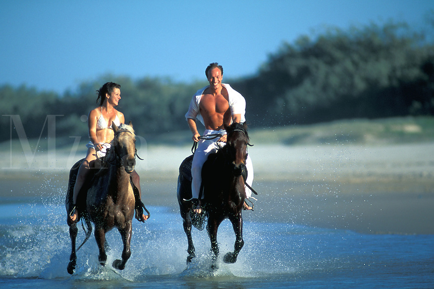 Australia, Queensland, happy couple galloping horses on beach.  MR available