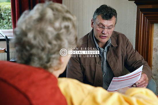 Welfare rights worker reading back completed form to check information is correct,