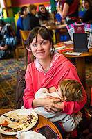 Portrait of a mother breastfeeding her child while sitting at a table during  a sling meet held in the family restaurant and play area in a pub.