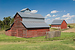 Two red barns, clouds, rusting farm machinery, Kansas