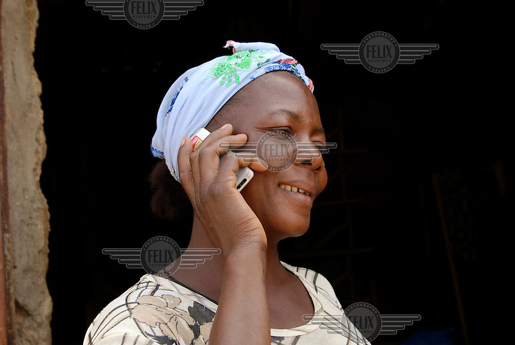 38 year old Farmer Mone Alassane talking on her mobile phone. Supported by IFAD, the International Fund for Agricultural Development, PAMER (Projet d?Appui aux Micro Entreprises Rurales) provides farmers with training and support to develop micro-enterprises in rural areas of Burkina Faso.....