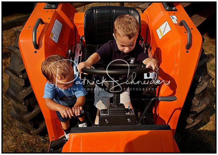 Two young boys try out a tractor, which was on display at a county fair.  Model released image can be used to illustrate many purposes.