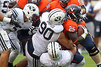 Virginia running back Kevin Parks (25) is tackled by Brigham Young defensive lineman Bronson Kaufusi (90) during the first half of the game in Charlottesville, Va. Virginia defeated Brigham Young 19-16. Photo/Andrew Shurtleff