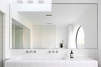 A large mirror hangs above a functional tiled washbasin in a modern white minimalist bathroom. The mirror reflects a wall mounted cupboard and gives the room a sense of space.