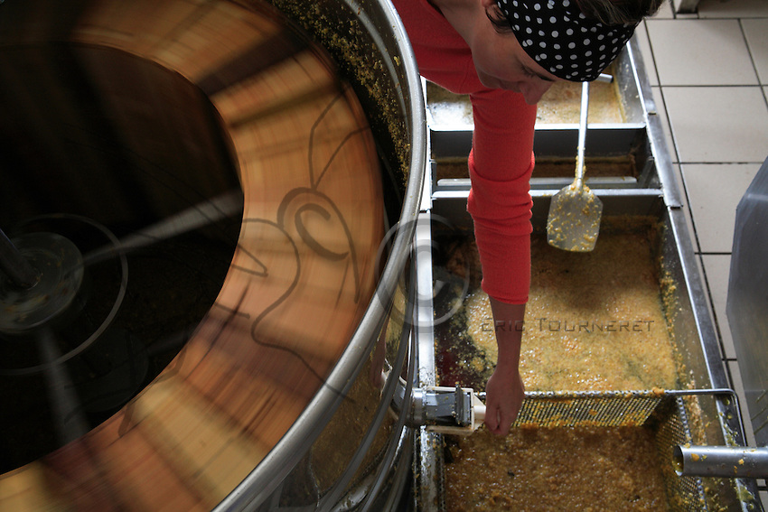 Work in the honey house is very methodical: The shallow frames of a harvest pass one by one through an uncapping machine. Into the vat fall the cap and a tiny amount of honey, which will later be recovered. The frame is inspected by hand to ensure that it has been completely uncapped, and then the frames are placed in a rotary extractor, where honey is extracted from the cells by centrifugal force. It is then filtered to remove the wax particles. Afterwards, it is aged for several days at a constant temperature to let the air and last wax residue rise to the surface, then is poured into pots or jars.