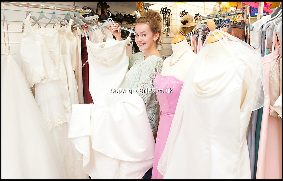 BNPS.co.uk (01202) 558833<br /> Picture: LauraJones/BNPS<br /> <br /> Amelia Platt picking out a wedding dress.<br /> <br /> A charity shop is being besieged by bargain-hunting brides after a mystery donor gave them 100 new wedding dresses.<br /> <br /> Staff at the PDSA store in Boscombe, Bournemouth, Dorset, were shocked when they opened several cardboard boxes left for them to find the pristine wedding and bridesmaid gowns inside.<br /> <br /> The garments have a combined retail price of more than &pound;50,000 but the charity shop is selling them for huge discounted prices. One gown worth &pound;1,500 is for sale for &pound;250.