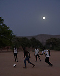 Young men play football in the moonlight in Kauda, a village in the Nuba Mountains of Sudan. The area is controlled by the Sudan People's Liberation Movement-North, and frequently attacked by the military of Sudan. The Catholic Church sponsors schools and health care facilities throughout the war-torn region.