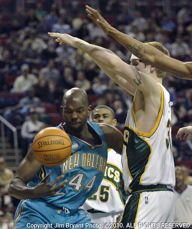 New Orleans Hornets' Marc Jackson, left, looses the ball while being guarded by Seattle SuperSonics' Robert Swift, right, during the second quarter of an NBA basketball game Tuesday, Feb. 28, 2006, in Seattle. Sonics' Earl Watson, behind, helps out. .. Jim Bryant Photo. ©2010. All Rights Reserved.