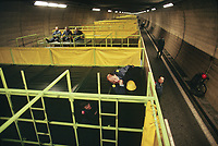 Switzerland. Canton Lucerne. People lying on bunk beds in the Sonnenberg tunnel in Lucerne during the largest civil defense exercise ever held in the country. From 16 to 21 November 1987, almost 1200 men and women converted a motorway tunnel into perhaps the world's largest bunker structure. The civil protectors had to prove during the exercise «Ameise» ( Ants in english) that in an emergency more than 20,000 inhabitants of the city of Lucerne could survive here in the mountain for two weeks. The Sonnenberg Tunnel is a 1,550m  long motorway tunnel, constructed between 1971 and 1976. At its completion it was also the world's largest civilian nuclear fallout shelter, designed to protect 20,000 civilians in the eventuality of war or disaster. Based on a federal law from 1963, Switzerland aims to provide nuclear fallout shelters for the entire population of the country. The construction of a new tunnel near an urban centre was seen as an opportunity to provide shelter space for a large number of people at the same time. The giant bunker was built between 1970 and 1976 at a cost of 40 million Swiss francs. The shelter consisted of the two motorway tunnels (one per direction of travel), each capable of holding 10,000 people in 64 person subdivisions. A seven story cavern between the tunnels contained shelter infrastructure including a command post, an emergency hospital, a radio studio, a telephone centre, prison cells and ventilation machines. The shelter was designed to withstand the blast from a 1 megaton nuclear explosion 1 kilometer away. The blast doors at the tunnel portals are 1.5 meters thick and weigh 350 tons. The logistical problems of maintaining a population of 20,000 in close confines were not thoroughly explored, and testing the installation was difficult because it required closing the motorway and rerouting the usual traffic. The only large-scale test, a five-day exercise in 1987 to practice converting the road tunnels into usable shelters, reveale