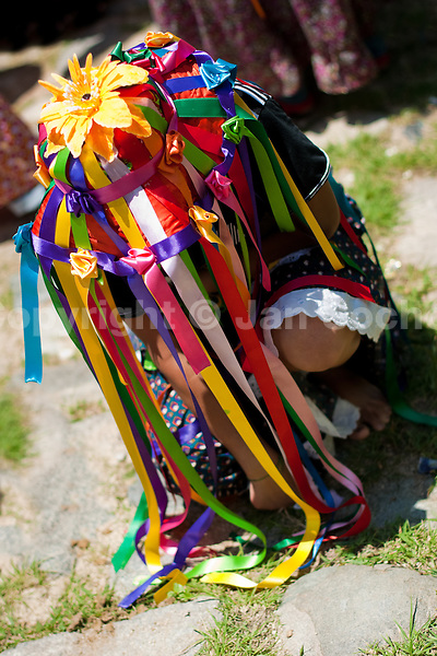 """A Negritas dancer with colorful ribbons on a hat kneels down in the religious procession in Atanquez, Sierra Nevada, Colombia, 3 June 2010. A colorful celebration of Corpus Christi is held in the Kankuamo Indians territory every year. """"The Dance of the Devils"""" is an ancient tradition kept for centuries on the Colombia's Caribbean coast. This Christian religious event usually coincides with the summer solstice, which has always been the key point for the native cultures and for the black African slaves. Due to this confluence, the Kankuamo myths, the African animistic rites and other Pre-Columbian features have blended with the Spanish Catholic festival into a lively spectacle."""