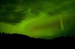 Northern lights (aurora borealis) at third quarter moon rising near the Rocky Mountains, Sentinel Range along Trout River