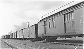 #62 combined RPO &amp; baggage car at Antonito.  Handrail on roof.  In a train of boxcars and gondolas.  Angled side view.<br /> D&amp;RGW  Antonito, CO  8/30/1941