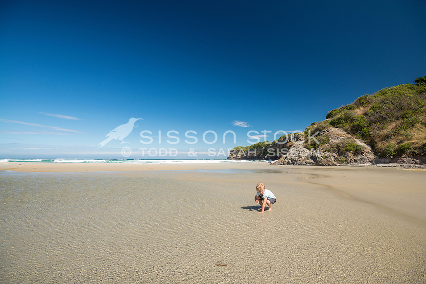 Young boy playing in the sand on Tomahawk Beach on a sunny blue sky day, Dunedin, Otago, South Island, New Zealand - stock photo, canvas, fine art print