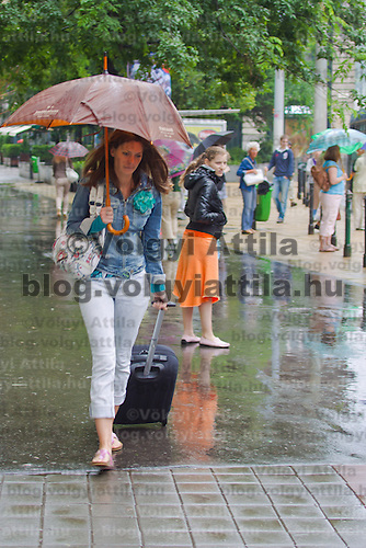 Commuters walk in rain fall in central Budapest, Hungary on June 16, 2010. ATTILA VOLGYI