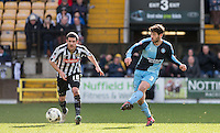 Joe Jacobson of Wycombe Wanderers plays a pass under pressure from Liam Noble of Notts County during the Sky Bet League 2 match between Notts County and Wycombe Wanderers at Meadow Lane, Nottingham, England on 28 March 2016. Photo by Andy Rowland.