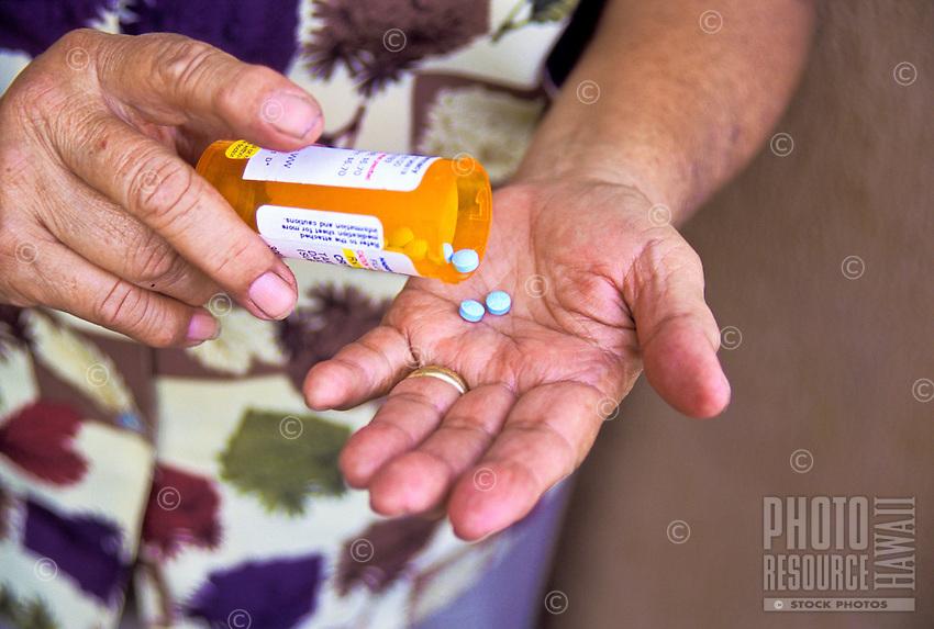 An elderly part-Hawaiian woman empties pills from a prescription container into her hand.