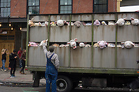 """Banksy enthusiasts flock to the trendy Meatpacking District in New York on Friday, October 11, 2013 to see the eleventh installment of Banksy's art, """"The Sirens of the Lambs"""". This particular sculptural piece consists of a slaughterhouse truck filled with bleating plush animals, controlled by puppeteers, which were driven around by a driver,center, who remained in character. The elusive street artist is creating works around the city each day, during the month of October accompanied by a satirical recorded message parodying a museum tour which you can get by calling the number 1-800-656-4271 followed by  # and the number of artwork.  (© Frances M. Roberts)"""