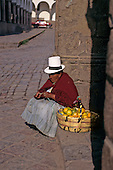 Cusco, Peru. Woman in traditional white felt hat selling oranges from a basket on the corner of a street.