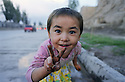 Interrupted while playing in a roadside puddle, a little Uighur girl shows an enthusiastic sign for peace.