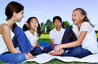 4 diverse children sitting on a blanket in a park with smiles and laughter