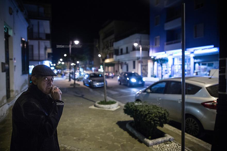 Taurianuova, Calabria, 03.12.2014. En mann røyker sin tobakk rett rundt hjørnet for der de fatale skuddene falt i 2009. Bilder til feature om båndene mellom Vatikanet, Ndrangheta og den italienske stat. Foto: Christopher Olssøn.