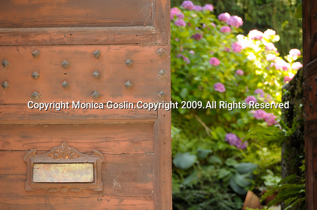 Looking through an opening in an old red door into a garden with pink flowers in Griante, a town on Lake Como, Italy.