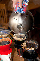 Making brewing filtered coffee by pouring hot water over coffee grounds. St Paul Minnesota USA
