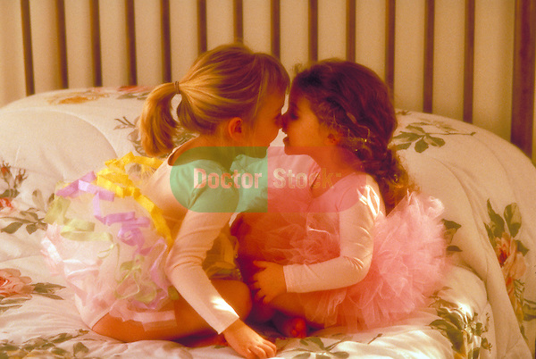 young girl ballerinas kissing on bed
