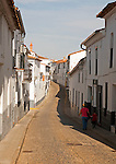 People walking along a quiet street in village of Jabugo, Sierra de Aracena, Huelva province, Spain
