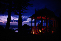 Lanterns illuminate a couple dusk as they stand in a gazebo that overlooks the Pacific coast after winter rains.