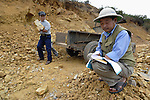 Luu Van Lam (left) loads rocks in a quarry in Ha Trach, Vietnam, while Luu Trung Truc keeps track of what's loaded. Both are landmine survivors and members of a self-help group of survivors and other people with disabilities.