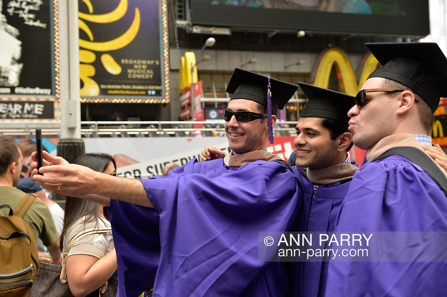 Manhattan, New York, U.S. - May 21, 2014 - In Times Square, three young men who graduated from New York University School of Business that day, are wearing purple graduation robes and black mortar board hats, and taking Selfies photos with a cell phone, during a pleasant Spring day in Manhattan.