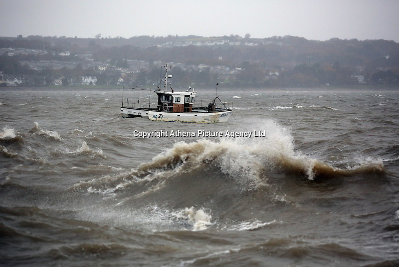 WEATHER WALES<br />Pictured: A boat bobs about in the waves in  Mumbles promenade in Swansea, Wales, UK. Monday 21 November 2016<br />Re: Flood warnings have been issued and Severe rain will be affecting most parts of Wales, UK