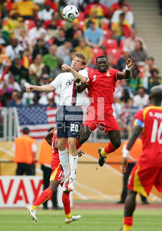 Brian McBride (20) of the USA goes up for a header with John Mensah (5) of Ghana. Ghana defeated the USA 2-1 in their FIFA World Cup Group E match at Franken-Stadion, Nuremberg, Germany, June 22, 2006. Ghana advances to round of 16 and the USA is out of the tournament.