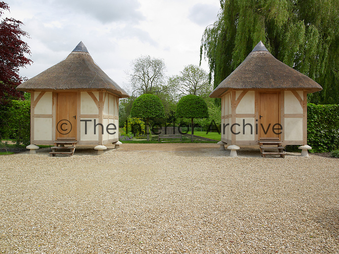 A pair of half-timbered thatched follies in the garden are raised on traditional stone supports