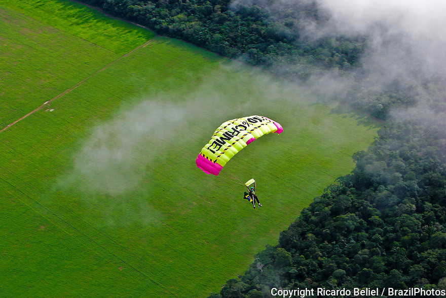"Greenpeace activist parachutes over a deforested area in Belterra, in the west region of Para state, Brazilian Amazon rainforest, with the message ""100% Crime"", to protest against the soy expansion which is leading illegal deforestation, land grabbing and violence against  local communities in the region. May 10th 2006, Brazil."