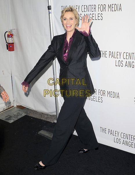 JANE LYNCH .at The PaleyFest 2011 Panel for Glee held at The Saban Theater in Beverly Hills, California, USA, March 16th,2011..full length grey gray black wide leg trousers jacket hand waving  purple shirt blouse                                                           .CAP/RKE/DVS.©DVS/RockinExposures/Capital Pictures.